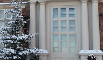 An image of an entrance door, Christmas tree and wreaths, in the snow, at Burton Agnes Hall