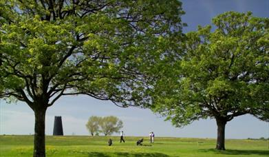 An image of the Black Mill on Beverley Westwood, with golfers on the golf course.