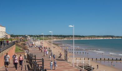 An image of people walking along the promenade and on the North beach at Bridlington