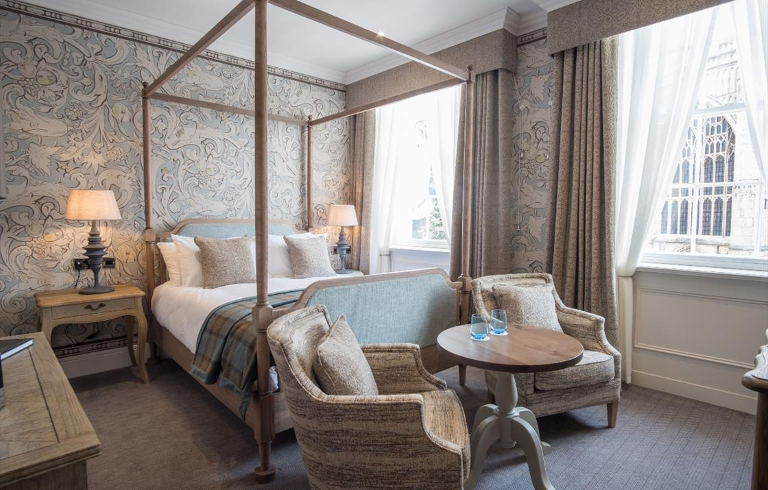 An image of a four poster bed and seating area in a double room.