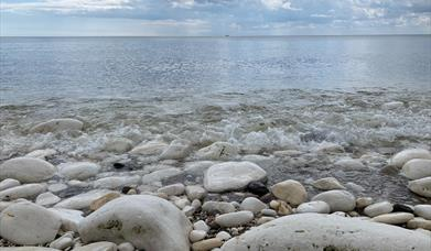 An image of stones and pebbles on the beach by the sea, with the tide coming in