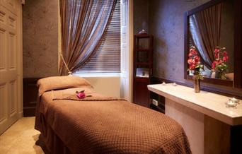 An image of a spa room, with cosy blanket on the massage couch & candles lit