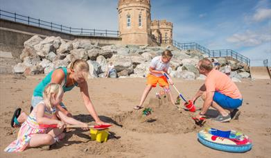 An image of a family making sandcastles on the beach at Withernsea, with the towers in the background